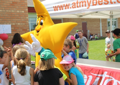 At the My Best Play day school event, children surround and embrace Ray the star.